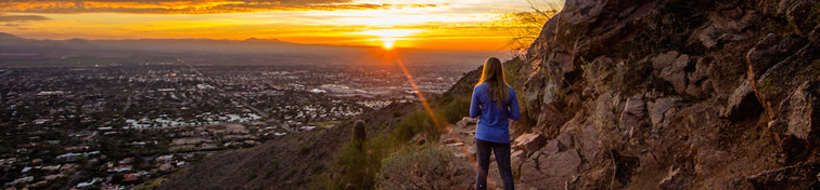 Woman watching sunrise from a mountain in Phoenix, Arizona