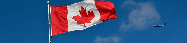 Airplane flying by a waving Canadian flag