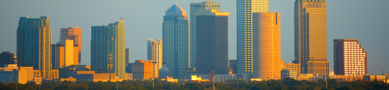A plane taking off from TPA Airport with the Tampa skyline in the background